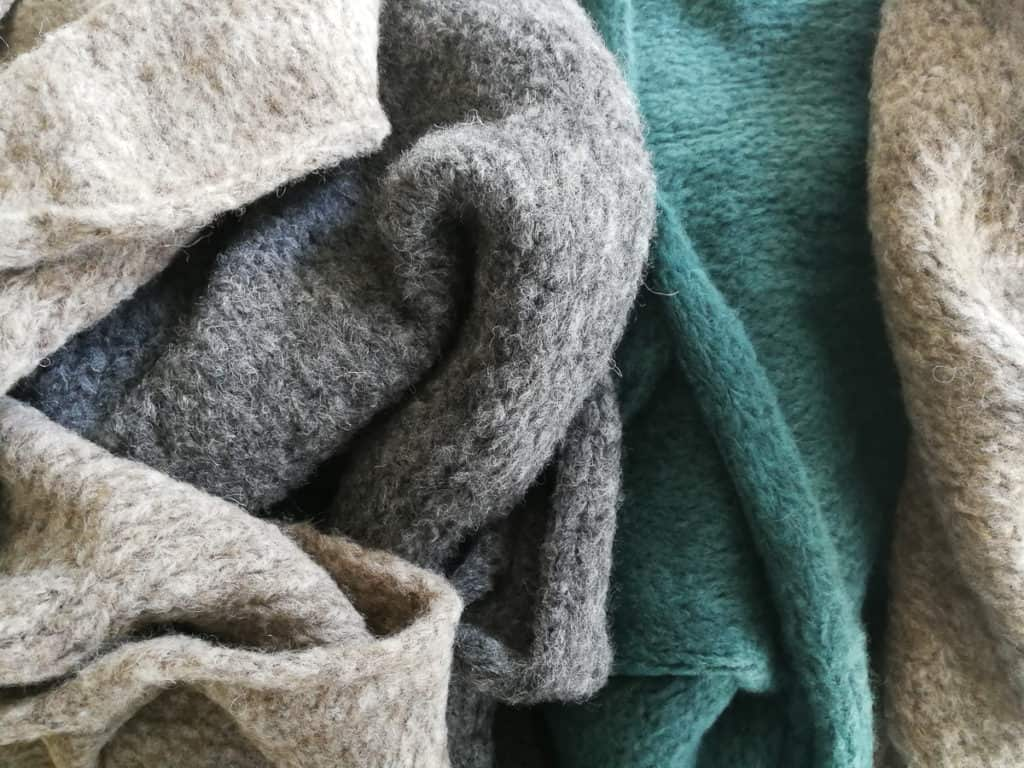 Combination of scarves made of baby alpaca and merino wool. They look very fluffy and bulky. Light grey, greenish and light brown colors.